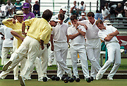 Members of the Northern Ireland lawn bowling team (R) watch the final shot by the South African team during gold medal lawn bowls at the Commonwealth Games in Victoria, BC. (1994)
