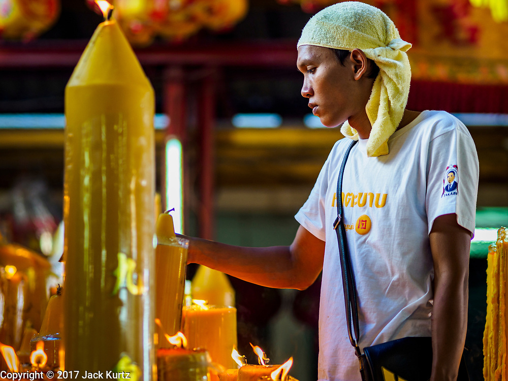 20 OCTOBER 2017 - BANGKOK, THAILAND: A volunteer cleans prayer candle at Chao Zhou Shi Kong Shrine in Bangkok's Chinatown on the first day of the Vegetarian Festival, what Thais call the Taoist Nine Emperor Gods Festival, in the Chinatown neighborhood of Bangkok, Thailand. It is a nine-day Taoist celebration beginning on the eve of 9th lunar month of the Chinese calendar. For nine days people participating in the festival wear only white and don't eat meat, poultry, seafood, and dairy products. The vegetarian festival is celebrated throughout Thailand, but especially in Phuket and Bangkok, cities with large ethnic Chinese communities.       PHOTO BY JACK KURTZ