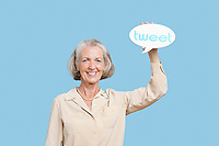 Portrait of senior woman holding tweet bubble against blue background
