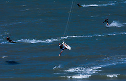 Kitesurfers fly through the air over the waters of the North Sea. (Photo © Jock Fistick)