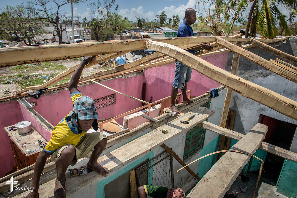 Men rebuild and repair a roof at a home damaged by Hurricane Matthew on Wednesday, Oct. 12, 2016, in Les Cayes, Haiti. LCMS Communications/Erik M. Lunsford