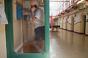 An elderly prisoner makes a telephone call in the wing call box. HMP Kingston, Portsmouth, United Kingdom. Kingston prison is a category C prison holding indeterminate sentenced prisoners.