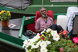 London, August 28 2017. A man dozes on his narrowboat on Day Two of the Notting Hill Carnival, Europe's biggest street party held over two days of the August bank holiday weekend, attracting over a million people. © Paul Davey.