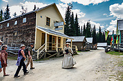 An actress in period costume conducts visitors on the Chinatown Tour in Barkerville Historic Town & Park, in British Columbia, Canada. Historically the main town of the Cariboo Gold Rush, Barkerville is now the largest living-history museum in Western North America. The town was named after Billy Barker from Cambridgeshire, England, who struck gold here in 1861, and his claim became the richest and the most famous. This National Historic Site nestles in the Cariboo Mountains at elevation 1200m (4000ft), at the end of BC Highway 26, 80 kilometres (50 mi) east of Quesnel. Gold here was first discovered at Hills Bar in 1858, followed by other strikes in 1859 and 1860. Wide publication of these discoveries in 1861 began the Cariboo Gold Rush, which reached full swing by 1865 following strikes along Williams Creek.