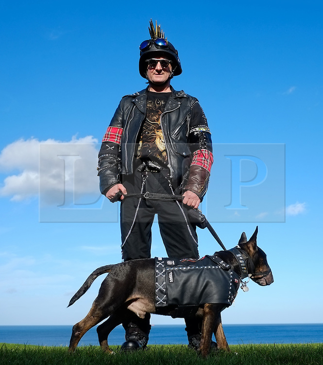 © Licensed to London News Pictures. <br /> 01/11/2014. <br /> <br /> Whitby, Yorkshire, United Kingdom<br /> <br /> Paul Ross and his dog Jack from Birtley come dressed as Steampunks to the Whitby Goth Weekend. <br /> <br /> The event this weekend brings together thousands of extravagantly dressed followers of Victoriana, Steampunk, Cybergoth and Romanticism who all visit the town to take part in celebrating Gothic culture. This weekend marks the 20th anniversary since the event was started by local woman Jo Hampshire.<br /> <br /> Photo credit : Ian Forsyth/LNP
