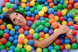 Teenage girl with physical disability lying in ball pool in residential respite care home,