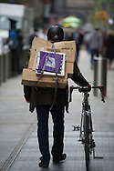 man with cardboard boxes on his back and a bike walking on a street in a city