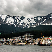 The town and port of Ushuaia at dusk with heavy cloud cover, with the dramatic snow-covered mountains behind.