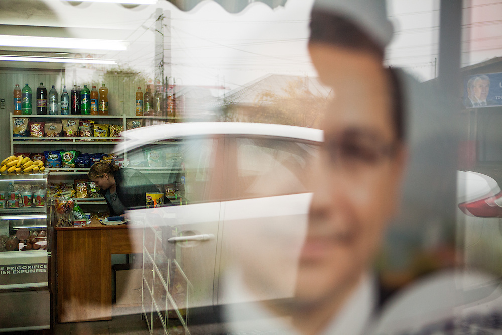 Grocery store owner Vali Coanca - who has Roma ethnicity -  is running since 20 years together with her family their own shop located at the main road in Marginenii de Jos. On the window a political advertisement for presidential candidate Victor Ponta.