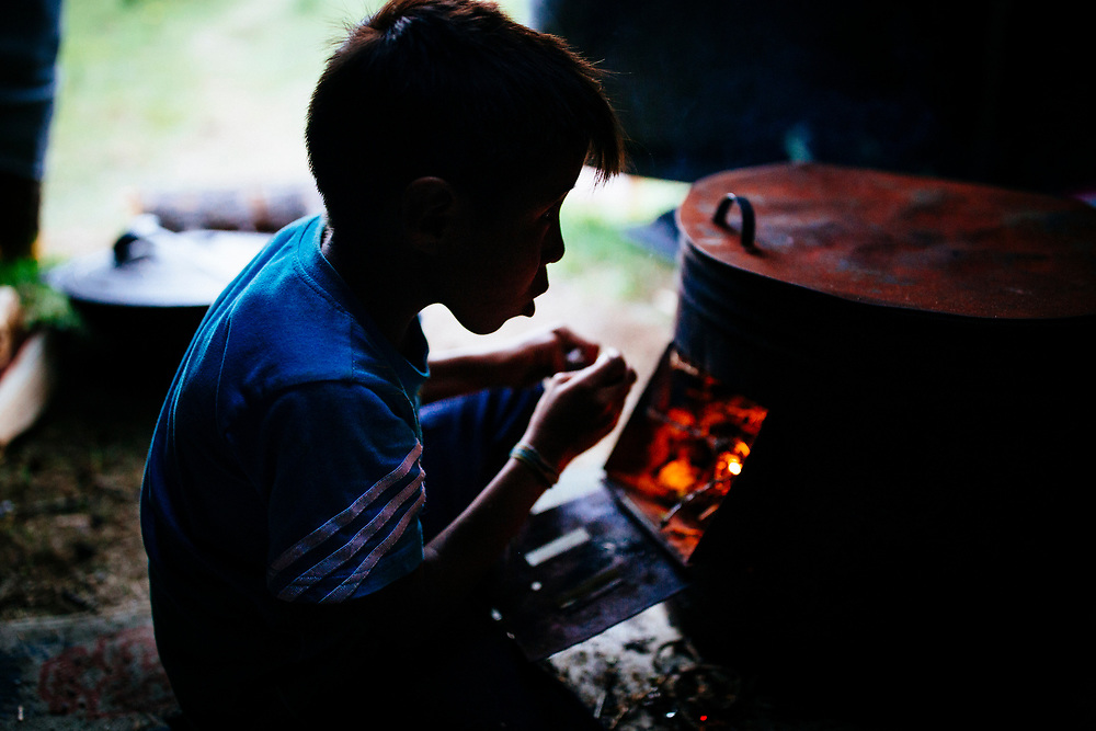 A young boy lights a fire in a nomadic tent in northern Mongolia.