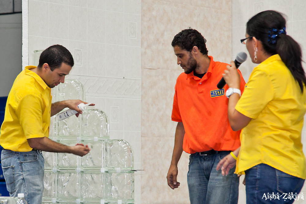 "(L-R) Carlos Garcia, Gavin Turbe, and Sol Acevedo of Home Depot's ""Do It Yourself Center"" present Laying Glass Blocks at the 2012 VIHFA Housing Expo; Mark C. Marin Center, Antilles School, Saturday, June 30, 2012.  © Aisha-Zakiya Boyd"