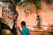 6th September 2014, New Delhi, India. An elephant handler decorates his elephant for an Indian wedding while a boy swings on a vine behind at New Rajinder Nagar, New Delhi, India on the 6th September 2014<br />