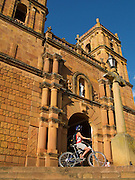 Cycling in the Colonial Barichara, in front of the 18th century sandstone Catedral Conception, Barichara - Colombia