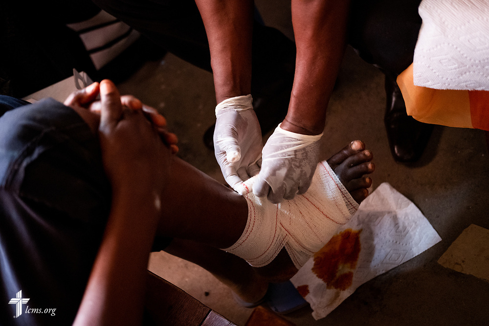 Michael Bio, a Sierra Leonean nurse studying to be a Community Health Officer, treats a patient with a foot wound on the fourth day of the LCMS Mercy Medical Team on Thursday, May 10, 2018, in the Yardu village outside Koidu, Sierra Leone, West Africa. LCMS Communications/Erik M. Lunsford