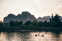 Children swim in a river at dusk in Vang Vien, Laos.