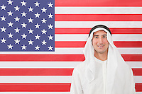 Portrait of an Arab man in traditional clothes looking away against American flag