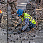 African American blue collar worker repairing and replace cobblestones on city street after underground repairs.<br />