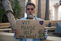 Portrait of homeless man with placard