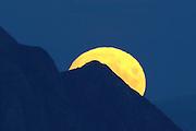 The full moon coming up behind a mountain   Fullmånen kommer opp bak et fjell.