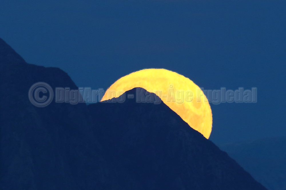 The full moon coming up behind a mountain | Fullmånen kommer opp bak et fjell.