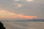 Nederland, Amsterdam, 20151028<br /> Zicht op het Noordzeekanaal bij Hembrug. De ochtend kondigt zich aan met oranje en gele kleuren door een gesloten wolkendek. Een klein schip vaart op het water<br /> Op de achtergrond opslagtanks langs de waterkant.<br /> Chemtura een fabriek aan de Ankerweg in Amsterdam, waar onder andere gewasbeschermingsmiddelen geproduceerd worden<br /> <br /> Netherlands, Amsterdam, 20151028<br /> View of the North Sea at Hembrug. The morning announces itself with orange and yellow colors with a closed cloud cover. A small ship sails on the water<br /> In the background storage tanks along the waterfront.<br /> Chemtura a factory on the Ankerweg in Amsterdam, where among other plant protection products are produced