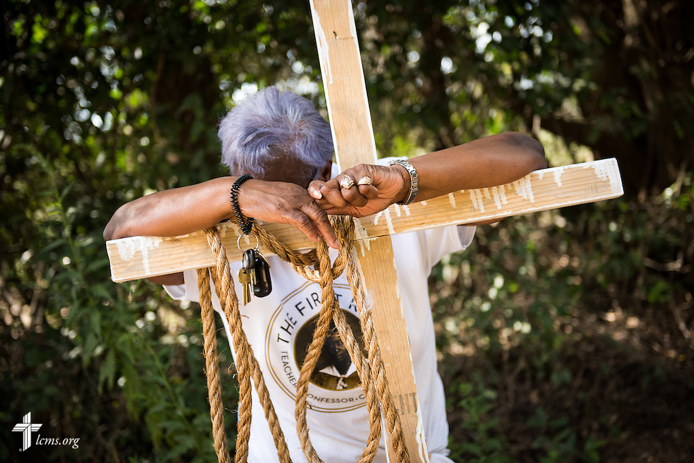 An assistant rests on a wooden cross during the long final day of filming for 'The First Rosa' documentary on Thursday, September 25, 2014, near Selma, Ala. LCMS Communications/Erik M. Lunsford
