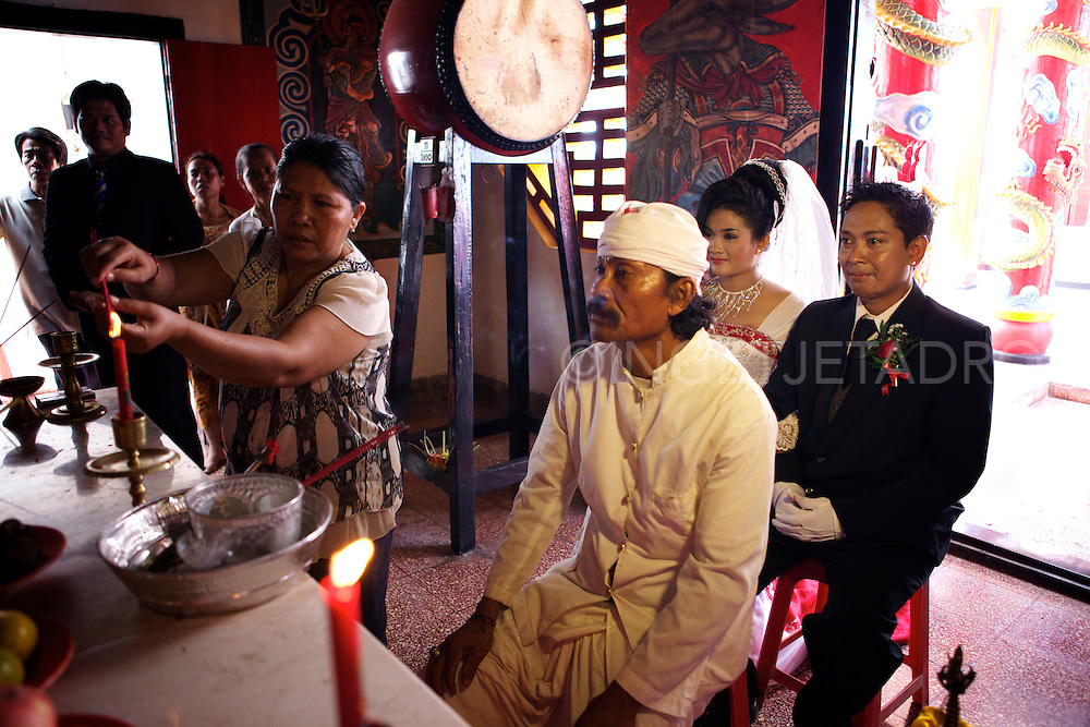 Chinese wedding Ceremony.<br /> This is the wedding between a Hindu groom (Dewa Nyoman Dinata) and his Budhist bride (Nyoman Candra Yuliani).<br /> <br /> There are 3 stages for this wedding as the bride will convert to Hindu.<br /> <br /> This is the 1st Ceremony - which is the Chinese wedding ceremony.<br /> <br /> A part of the Chinese wedding ceremony is when the bride gets picked up from the bride's house and the parents hand-over the bride with a ceremony following by praying to ask permission from Ancestors and parents and ask for a blessing.<br /> After this they will proceed to the Chinese Temple where the Ceremony is witnessed  by family and friends, except the parents.<br /> After this ceremony in the temple there is the &quot;Cisuak&quot; which is the releasing of 2 pigeons and after that releasing of coloured baloons.<br /> (Cisuak means: releasing a couple of pigeons which means releasing all the bad luck and wishing the good luck will come for their relationship in the future.<br /> <br /> After the Cisuak there is a Receiption Ceremony which is the chance  to say goodbye for the Bride from Parents, Family and Friends. <br /> Family usually do the &quot;Pay Teh&quot; Ceremony, which is that the bride and the groom will give a cup of tea and in return  they will receive a small present.<br /> <br /> &copy;Ingetje Tadros<br /> Lovina, Bali, 21-12-2012