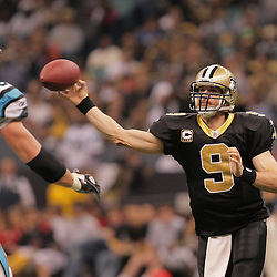 2008 December, 28: New Orleans Saints quarterback Drew Brees (9) throws a pass past Carolina Panthers defensive end Tyler Brayton (96) during a week 17 game between NFC South divisional rivals the Carolina Panthers and the New Orleans Saints at the Louisiana Superdome in New Orleans, LA.