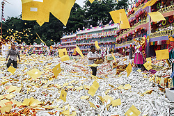 September 5, 2017 - Medan, North Sumatra, Indonesia - Ethnic-Chinese Indonesians throw 'hell money' as offerings for their ancestors' souls into the air during the 'hungry ghost' festival in Medan. During the month-long festival, Chinese people make offerings of food, hell money and paper-made models of items such as televisions, servants and cars to be burnt to appease the wandering spirits as it is believed that the gates of hell are opened during the month and their dead ancestors return to visit their relatives. (Credit Image: © Ivan Damanik via ZUMA Wire)