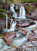 Baring Creek tumbles and falls over red sedimentary rocks in Glacier National Park, Montana, USA. Since 1932, Canada and USA have shared Waterton-Glacier International Peace Park, which UNESCO declared a World Heritage Site (1995) containing two Biosphere Reserves (1976). Rocks in the park are primarily sedimentary layers deposited in shallow seas over 1.6 billion to 800 million years ago. During the tectonic formation of the Rocky Mountains 170 million years ago, the Lewis Overthrust displaced these old rocks over newer Cretaceous age rocks.