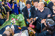 27 JANUARY 2014 - BANGKOK, THAILAND: LIKIT TARATIN, father of murdered anti-government protest leader Suthin Taratin, at the bathing rites for his son at Wat Sommanat Rajavaravihara in Bangkok. In Thai tradition, after death a bathing ceremony takes place in which relatives and friends pour water over one hand of the deceased. Suthin was a core leader of the People's Democratic Force to Overthrow Thaksinism (Pefot), one of several organizations leading protests against the elected government of Thai Prime Minister Yingluck Shinawatra. He was murdered Sunday, Jan. 28, while he was leading a rally to prevent voters from reaching a polling center in the Bang Na district of Bangkok.     PHOTO BY JACK KURTZ