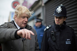 © licensed to London News Pictures. London, UK 25/03/2013.The Mayor of London Boris Johnson talking to a police officer as he joins members of the Dalston Safer Neighbourhood Team on their local beat to launch the Mayor's Police and Crime Plan on Dalston Kingsland High street in London. Photo credit: Tolga Akmen/LNP