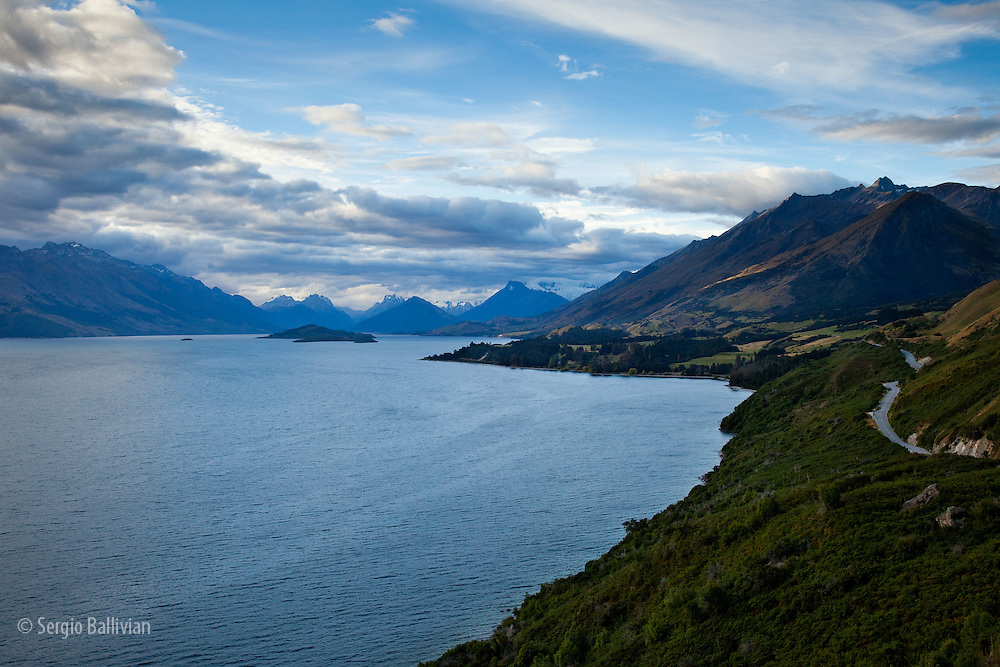 Storm clouds part to show the rugged Southern Alps and the road to Glenorchy above Lake Wakatipu, on New Zealand's south island.