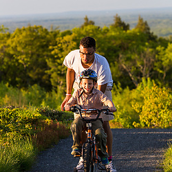 A teenage boy helps his young cousin ride a bike near the summit of Mount Agamenticus in York, Maine.