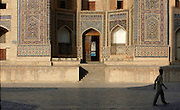 Low angle view of man passing in  front of the Mir-i-Arab Madrasah, 1535, Bukhara, Uzbekistan, pictured on July 8, 2010 in the afternoon. The Mir-i Arab Madrasah, which stands opposite the Kalyan Mosque was built by the Shaybany Ubaydallah Khan, and is still a functioning madrasah. Bukhara, a city on the Silk Route is about 2500 years old. Its long history is displayed both through the impressive monuments and the overall town planning and architecture. Picture by Manuel Cohen.