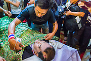 27 JANUARY 2014 - BANGKOK, THAILAND: A security guard in the anti-government movement pulls a funeral shroud up over Suthin Taratin during bathing rites for Suthin at Wat Sommanat Rajavaravihara in Bangkok. In Thai tradition, after death a bathing ceremony takes place in which relatives and friends pour water over one hand of the deceased. Suthin was a core leader of the People's Democratic Force to Overthrow Thaksinism (Pefot), one of several organizations leading protests against the elected government of Thai Prime Minister Yingluck Shinawatra. He was murdered Sunday, Jan. 28, while he was leading a rally to prevent voters from reaching a polling center in the Bang Na district of Bangkok.     PHOTO BY JACK KURTZ