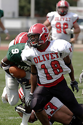 09 September 2006 Comet James Abbott blocks the path of Titan ball carrier Marcus Dunlop..In the first ever football competition between the Olivet Comets and the Illinois Wesleyan Titans, the Titans strut off the field with a 21- 6 victory. .Game action took place at Wilder Field on the campus of Illinois Wesleyan University in Bloomington Illinois.