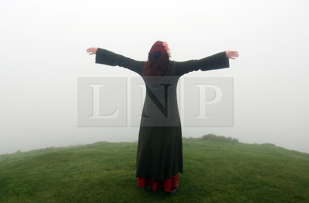 © Licensed to London News Pictures. 01/05/2014. Glastonbury, UK Archdruid of Glastonbury and Stonehenge Rollo Maughling and Cam Valley morris men amongst others welcome the May day sunrise from a foggy Glastonbury Tor in Somerset. . Photo credit : Jason Bryant/LNP