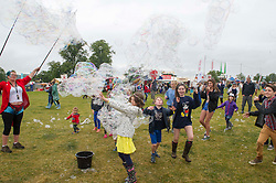 Image ©Licensed to i-Images Picture Agency. 05/07/2014. Oxford, United Kingdom. Cornbury Music Festival,The Great Tew Park, Chipping Norton.Oxfordshire.<br /> Picture Shows Festival goers enjoying the weather at Cornbury, kids keeping busy with bubbles. Picture by  i-Images