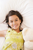 Girl lying on bed with teddy bear smiling half length