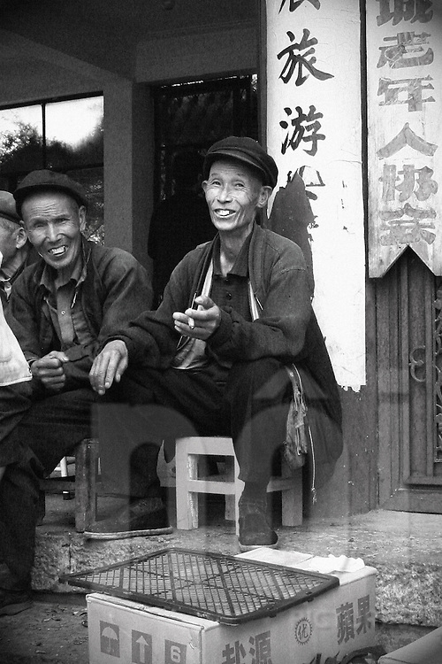 On the village place some old chinese men are talking and laughing. They wearing chinese flat cap. One guy is smoking. Wallpaper with chinese writes is stick on a pillar.
