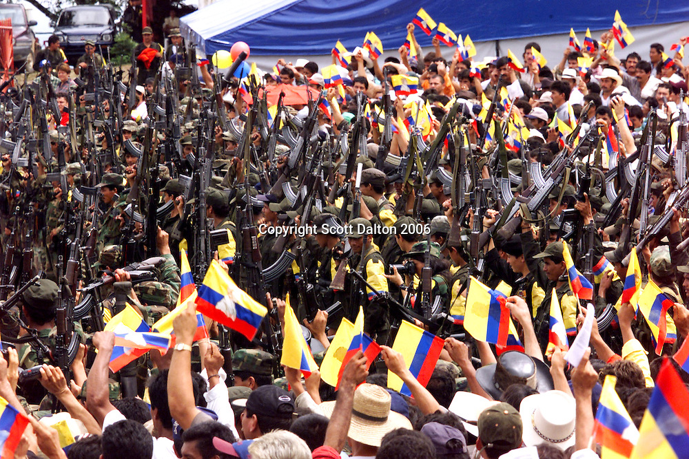 Rebels of the Revolutionary Armed Forces of Colombia, FARC, raise their guns as supporters wave flags at a ceremony outside of San Vicente del Caguan in the former FARC controlled zone of Colombia. The FARC are Colombia's oldest and largest rebel group numbering over 18,000 rebels. The U.S. government estimates that the rebels make 300 million dollars a year off of the drug trade. (Photo/Scott Dalton)