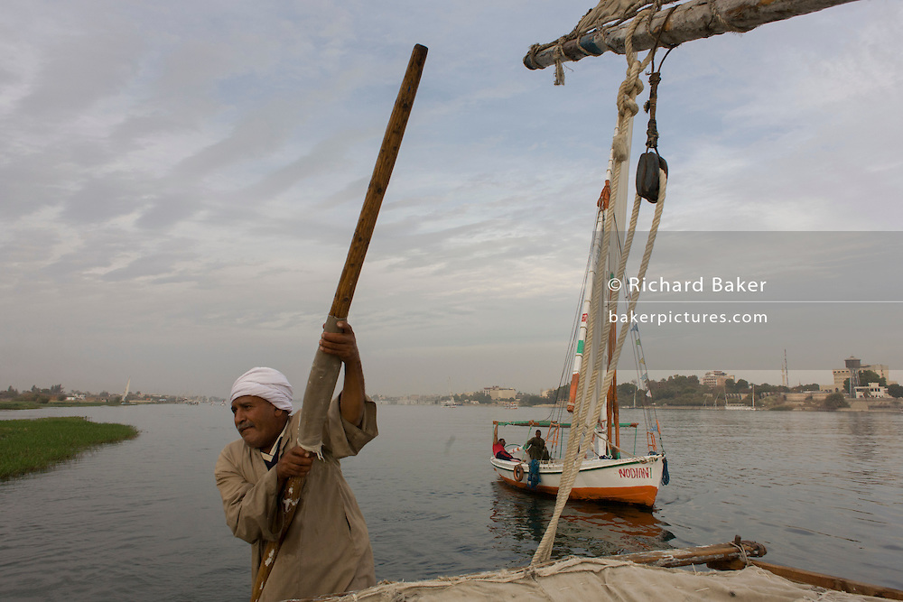 A crewman of a felucca pushes his boat away from the riverbank while sailing on the River Nile at Luxor, Nile Valley, Egypt. Feluccas are ancient Egyptian sail boats which were used in ancient times as a primary mode of transport and are the only type of boat that is still used extensively in the country.