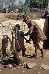 Man using a pump to fill a container at Gobindigahr; Punjab; India,