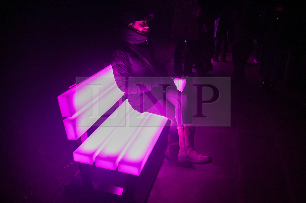 "© Licensed to London News Pictures. 15/01/2016. London, UK.  A woman sits on ""Lightbench"" by Bernd Spiecker for LBO-Lichtankobjekte in Grosvenor Square.  The work forms part of Lumiere London, a major new light festival which is into the second of four evenings and featuring artists who work with light.  The event is produced by Artichoke and supported by the Mayor of London.  Photo credit : Stephen Chung/LNP"