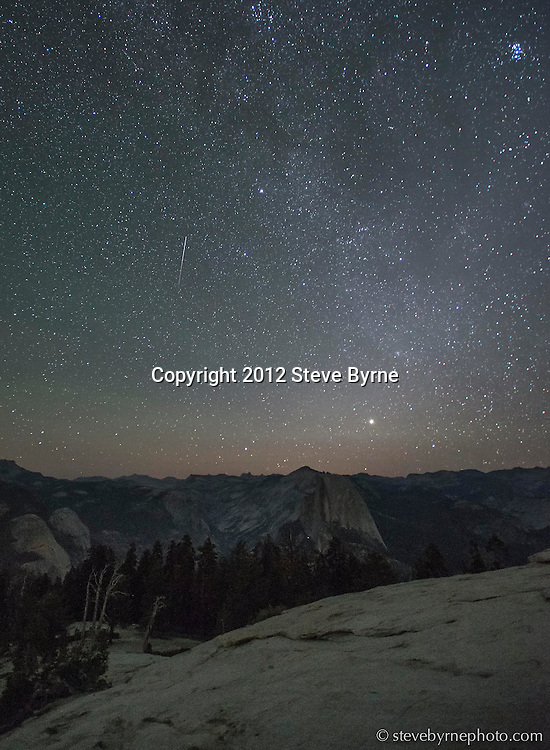 A meteor streaks through the night sky during the 2013 Perseid Meteor Shower over Half Dome and the High Sierra of Yosemite National Park, California.