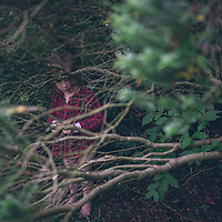 Young girl standing under tree branches outdoors in garden