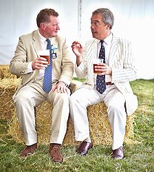 © Licensed to London News Pictures.  18/07/2014. WOODSTOCK, UK. UKIP leader Nigel Farage (right) shares a pint with Ross Murray (left), deputy president of the Country Land & Business Association, during a visit to the CLA Game Fair being held at Blenheim Palace near Oxford. Over 150,000 people are expected to visit the event over the weekend.  <br /> <br /> Photo credit: Cliff Hide/LNP