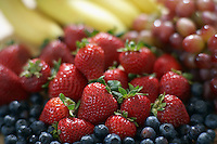 Blackberries strawberries grapes and bananas close-up selective focus