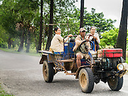 14 JUNE 2013 -  PANTANAW, AYEYARWADY, MYANMAR:  Women ride on trailer towed by a tractor used as a bus in the rain along Highway 5 in Pantanaw, Ayeyarwady, in the Irrawaddy delta region of Myanmar. This region of Myanmar was devastated by cyclone Nargis in 2008 but daily life has resumed and it is now a leading rice producing region.  PHOTO BY JACK KURTZ